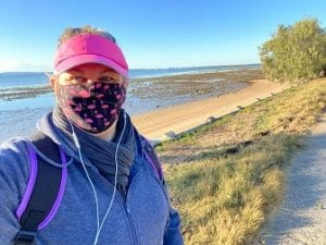 woman wearing a mask when going for a walk by the sea